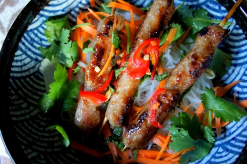 Vietnamese pork kebab (Nem Nuong) on noodles, salad and fresh herbs