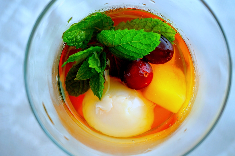 Summer ice tea, with chilled lychee flavored Chinese tea, lychee fruit, pineapple, cranberry, orange, lime, honey and mint